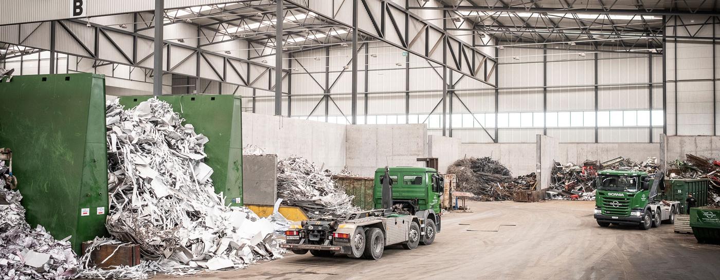 Industriehalle mit verschiedenen Abteilen für Recycling Abfällen und zwei grünen Lastwagen.