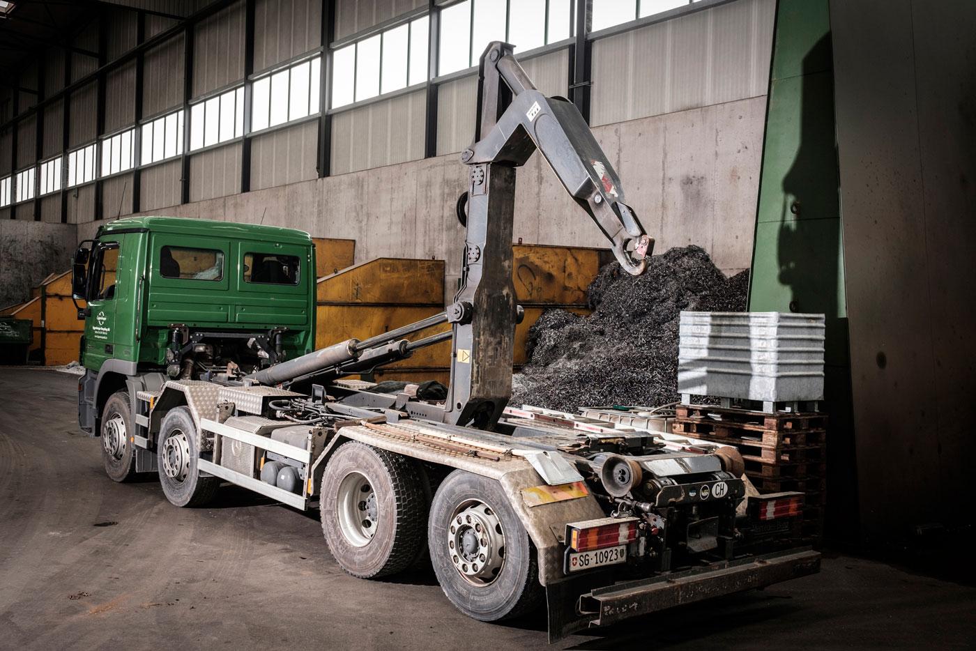 Grüner Lastwagen mit UT-Abrollkipper Saurier in Industriehalle.