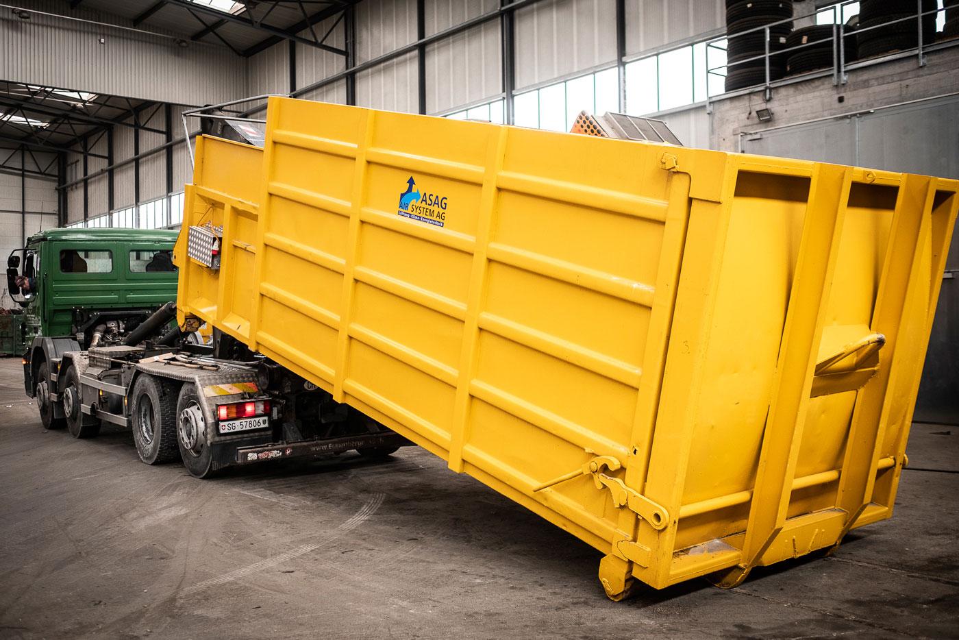 Lastwagen mit UT-Abrollkipper Saurier mit gelbem Container in Industriehalle.