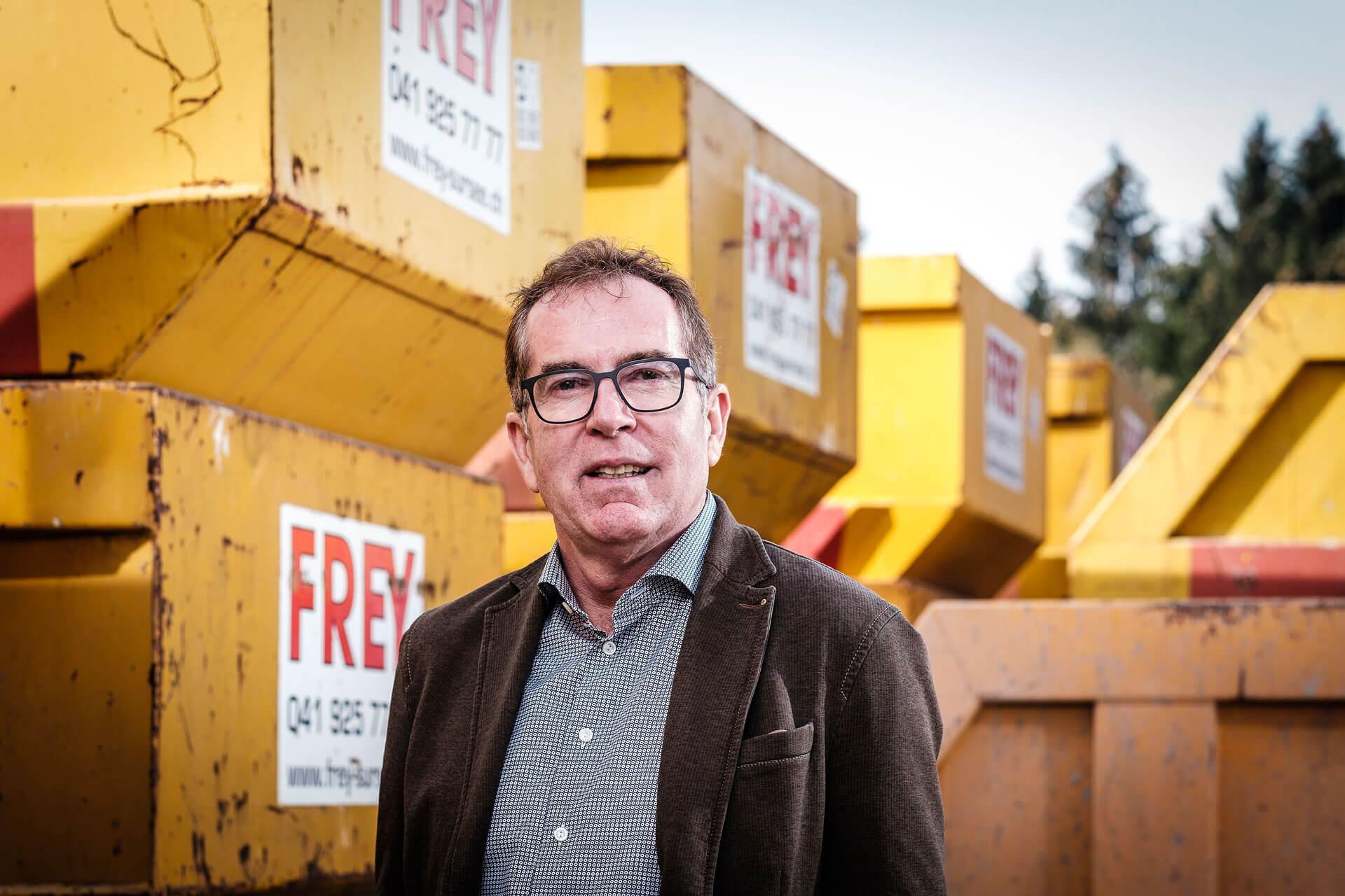 Geschäftsführer Bruno Frey steht vor gelben FREY Mulden vo UT.
