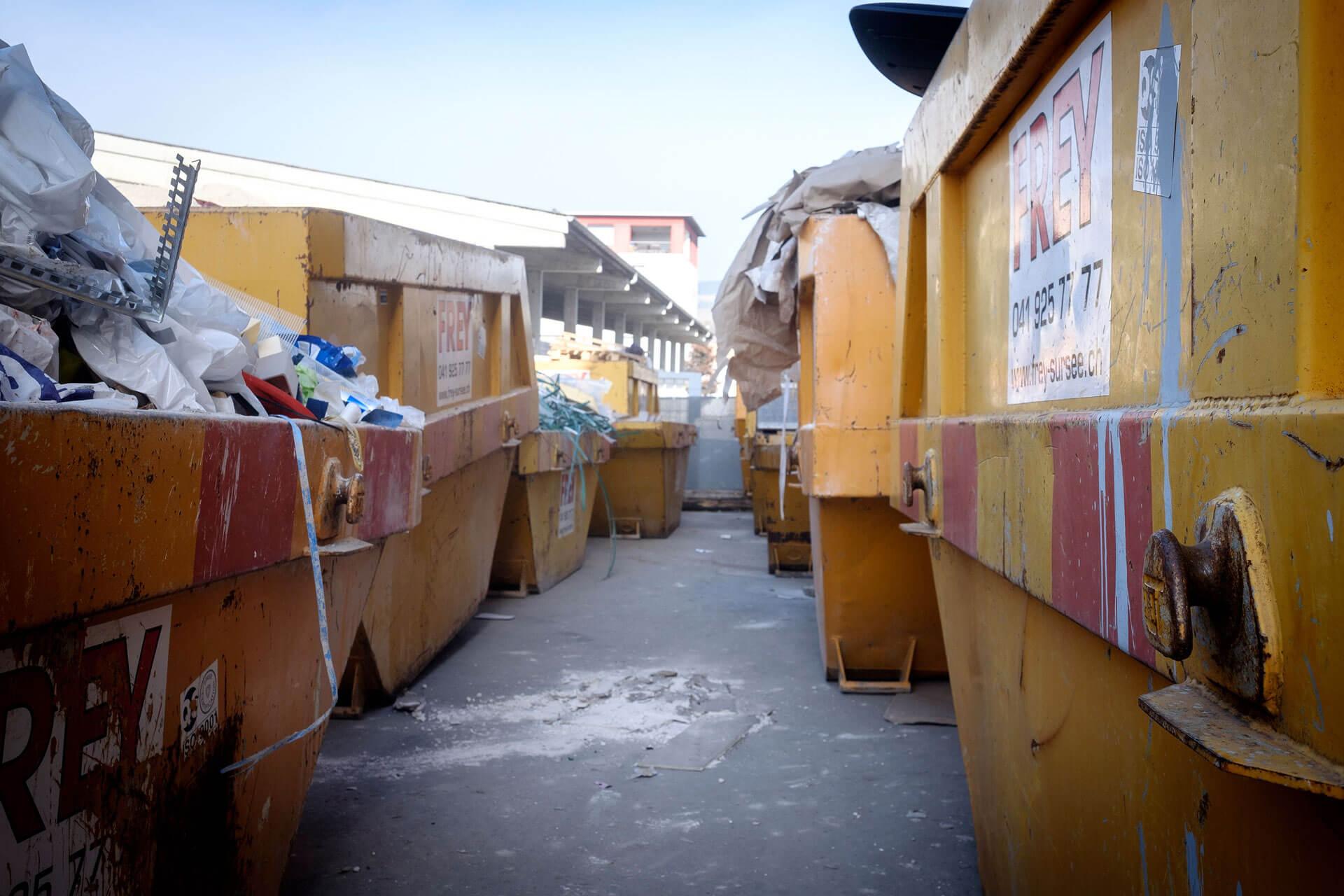 Gelbe Mulden gefüllt mit verschiedenen Recycling-Abfällen.