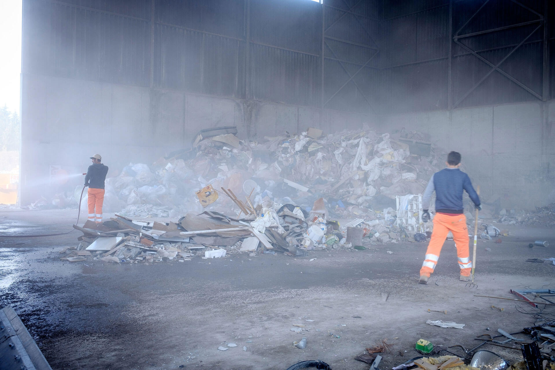Berg mit Recycling-Abfällen. Zwei Josef Frey AG Mitarbeiter sorgen für Ordnung.