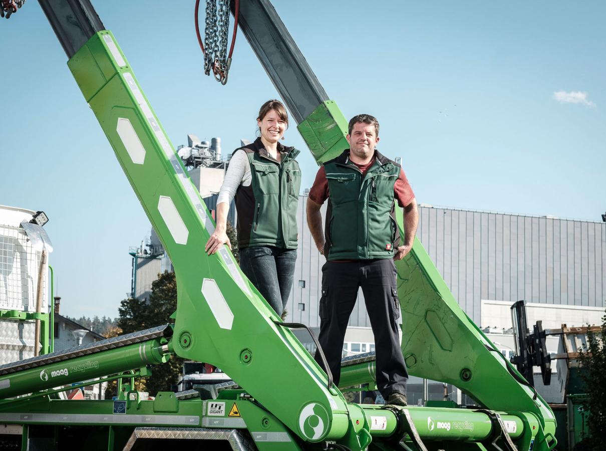 Judith Maag und Thomas Schwander stehen auf der Ladefläche eines Lastwagen mit hellgrünem UT-Absetzkipper als Aufbau. Industriegelände im Hintergrund.