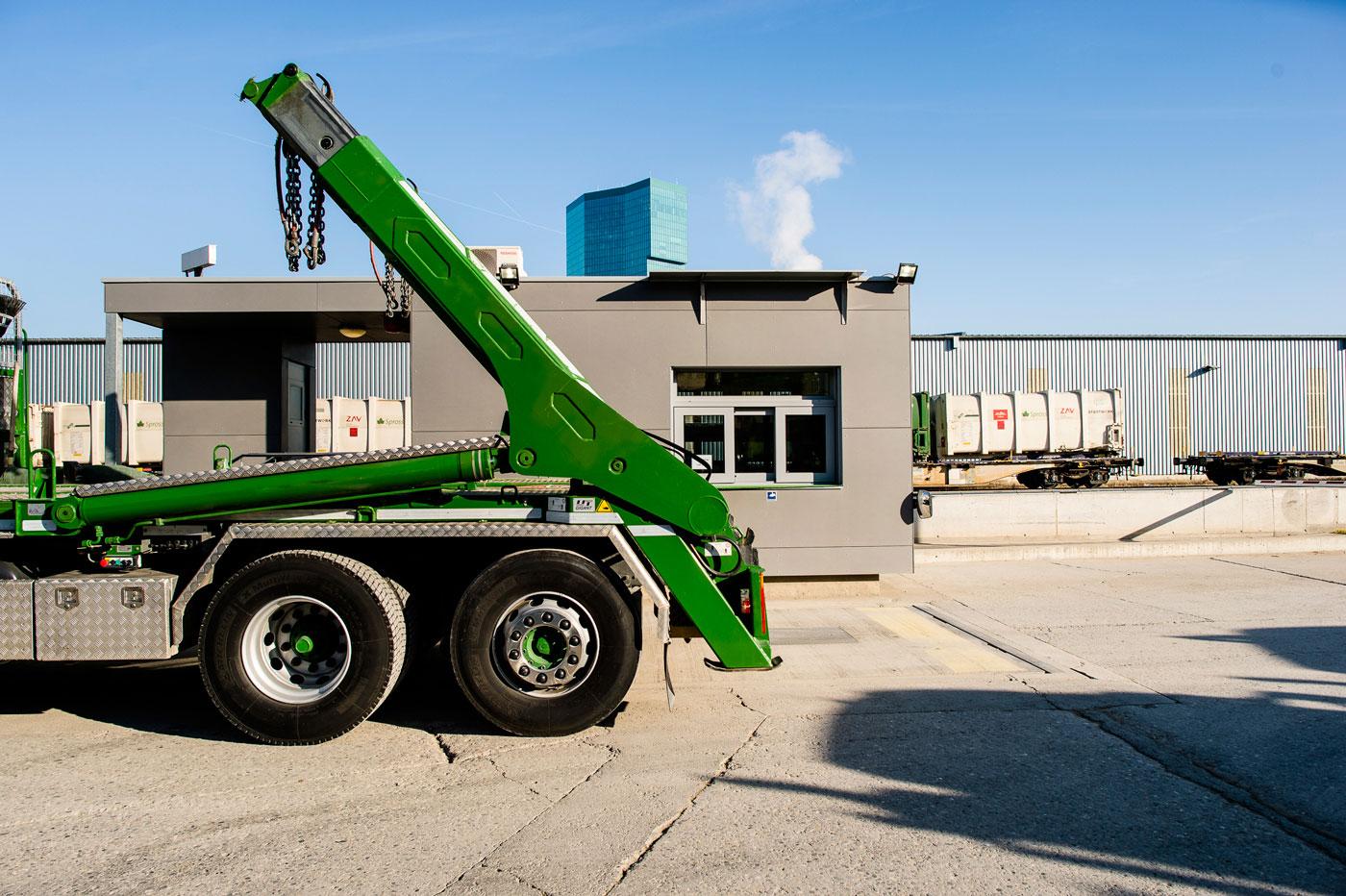 Ladefläche von grünem Lastwagen mit UT-Absetzkipper auf Industriegelände.