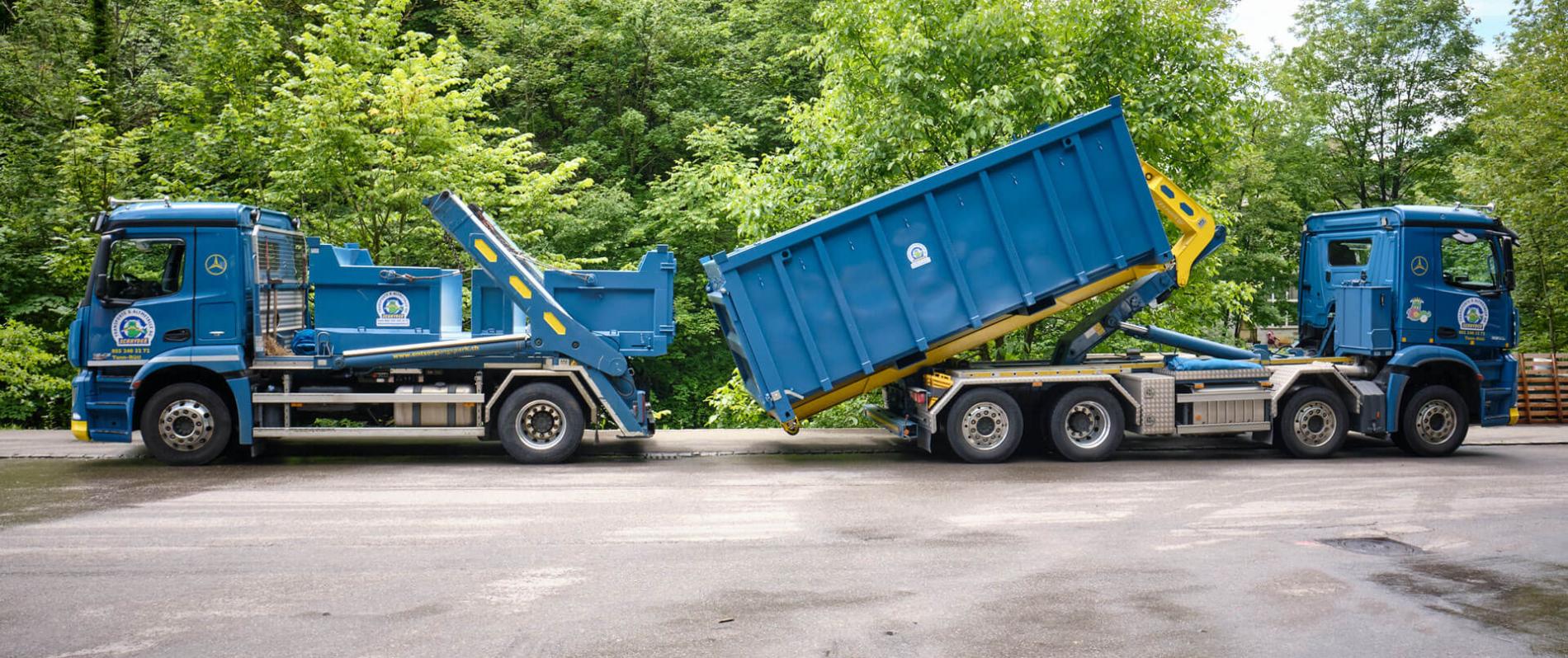 Ein blauer Lastwagen mit Absetzkipper-Aufbau und ein blauer Lastwagen mit Abrollkipper-Aufbau stehen sich auf einem Teerplatz vor Waldrand gegenüber.