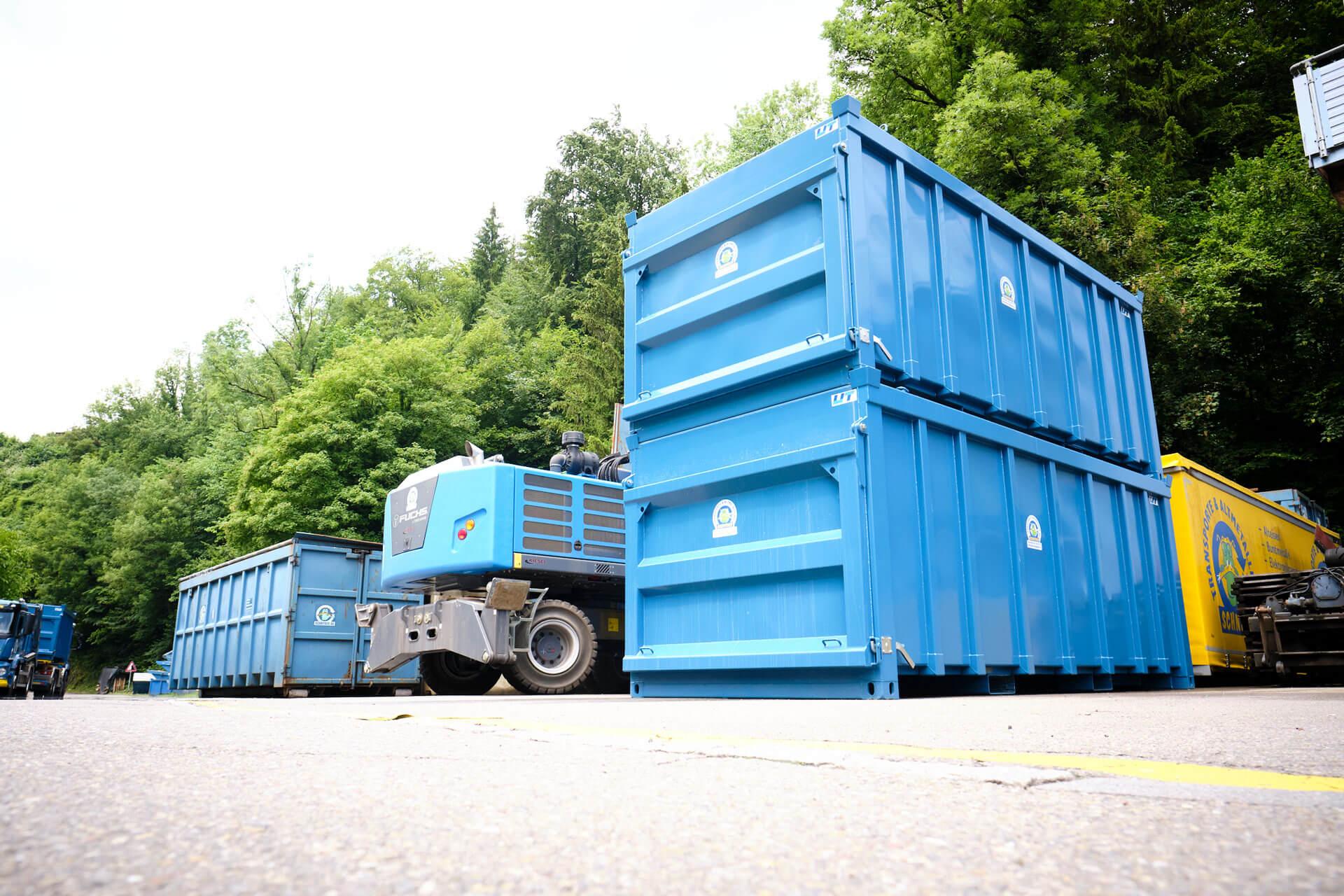 Zwei blaue Container aufeinander gestapelt mit weiteren Fahrzeugen im Hintergrund.