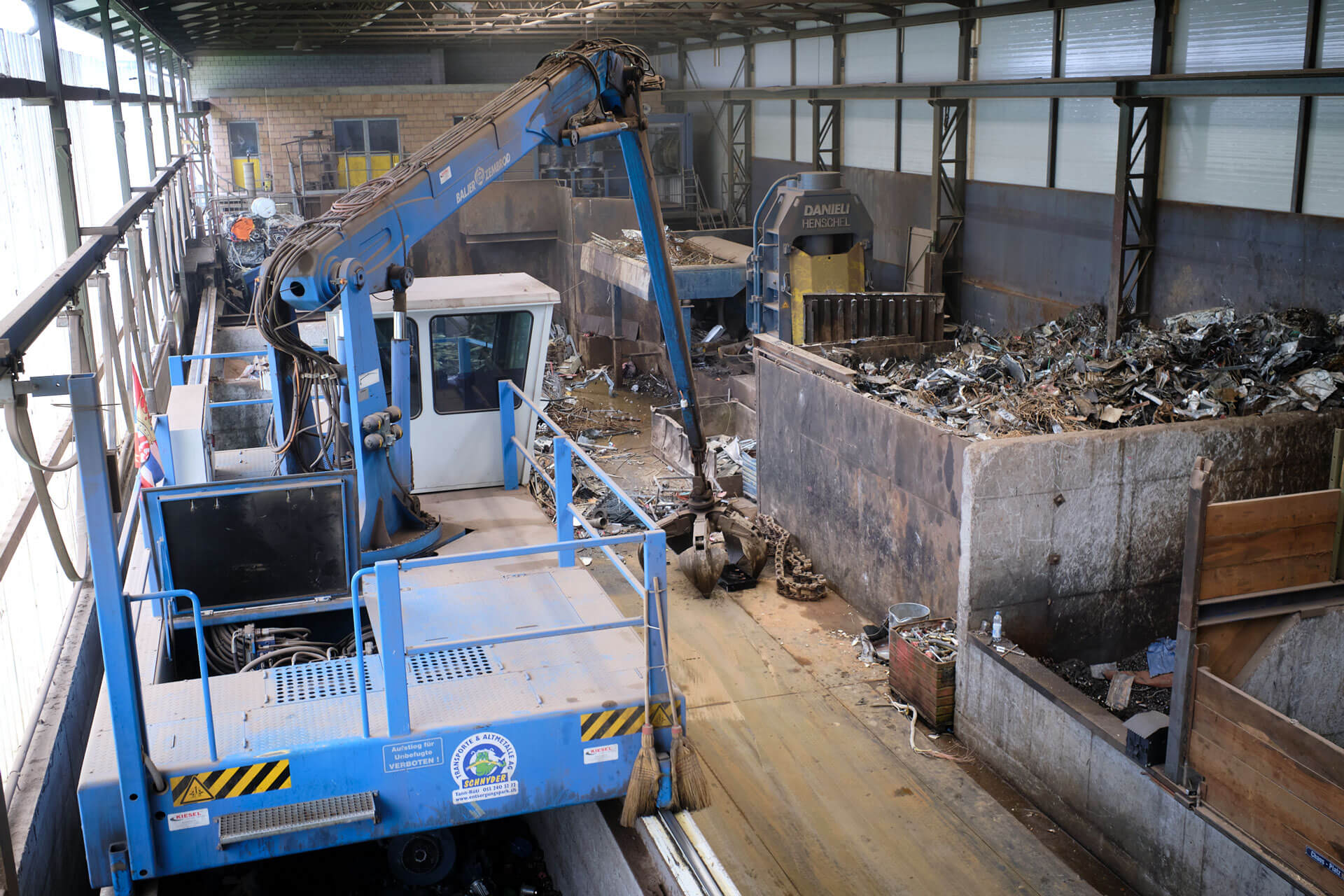 Halle mit Bagger, wo verschiedene Rohstoffe und Altmetalle aussortiert werden.