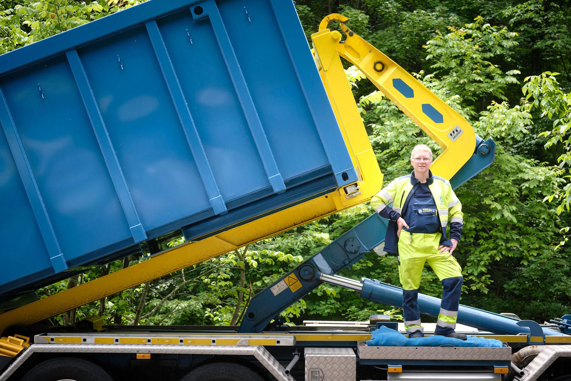 Geschäftsführer Jörg Schnyder steht auf blau gelbem Abrollkipper.