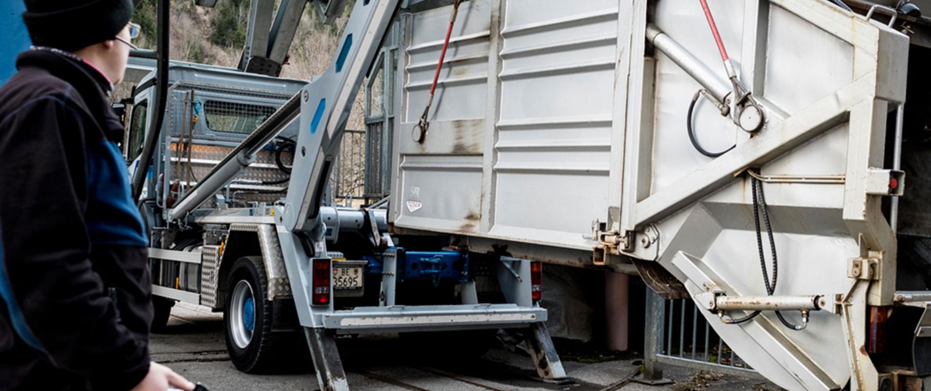 Grauer Lastwagen mit UT-Absetzkipper lädt Container ab.