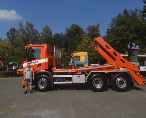 Fahrzeugtechniker Adrian Schildknecht vor orangem Brunner Umweltservice AG Lastwagen.