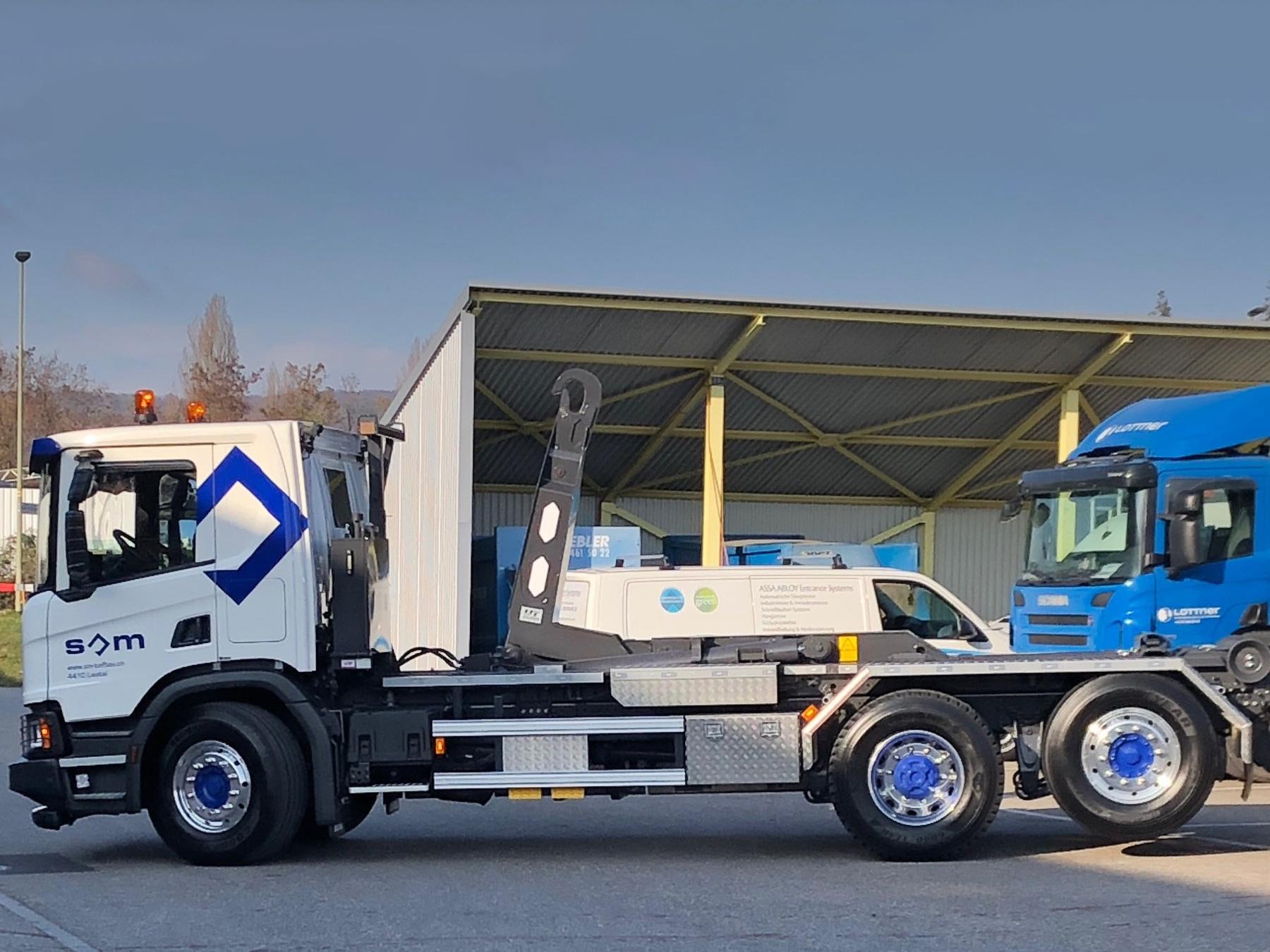 Welaki: Weisser 3-Achser Lastwagen mit UT Haken-Abrollkipper.