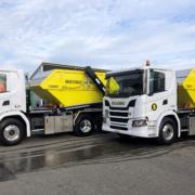 Zwei weisse Lastwagen mit gelben Mulden.