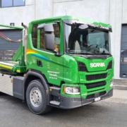 Grüner 3-Achser Lastwagen mit UT Absetzkipper.